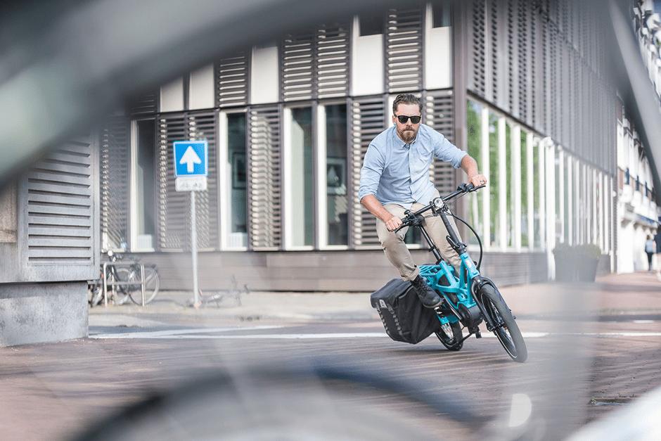 Mann fährt auf einem türkisen Fahrrad um eine Kurve