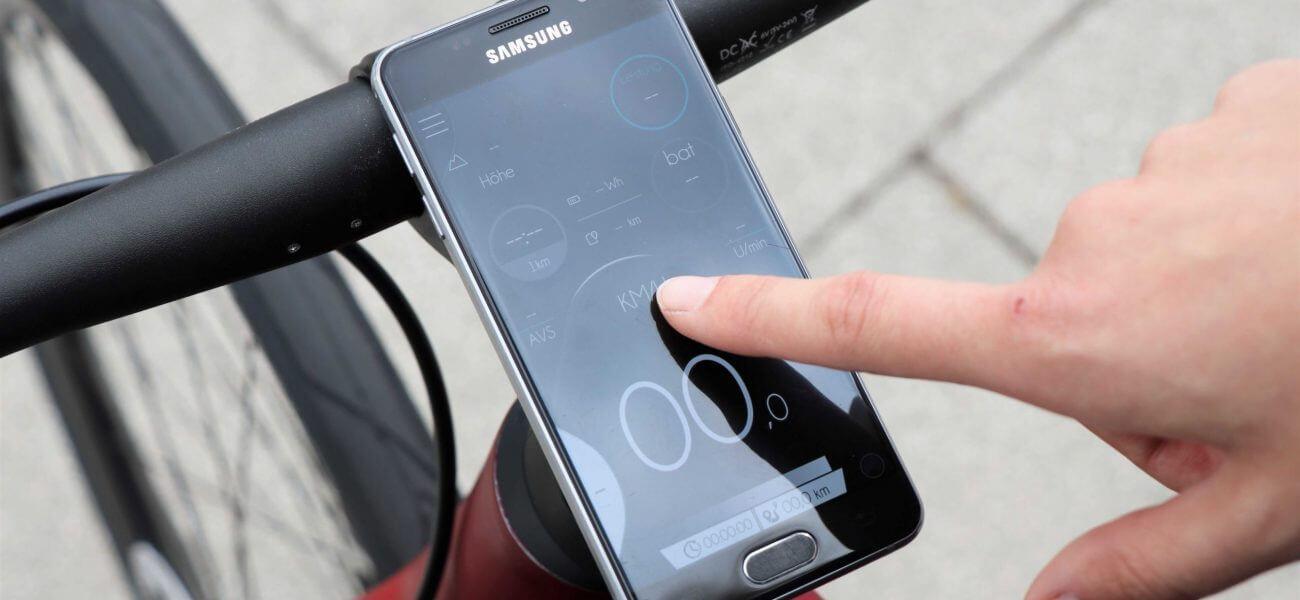 Person tippt auf ein Telefon, das als Tacho an einem Fahrrad befestigt ist